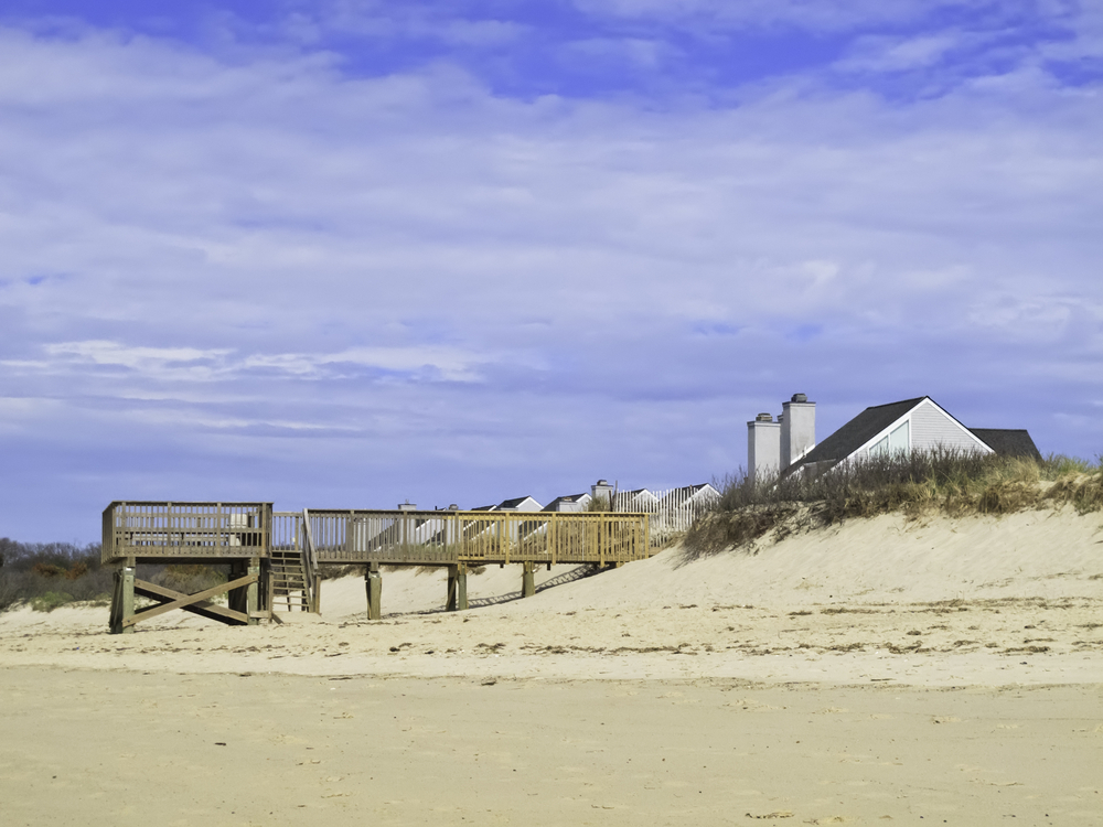 Coastal landscape Beach view of boardwalk and deck by dune near peaked roofs of houses in Cape Cod, Massachusetts