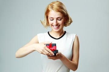 Happy beautiful young woman opening jewelery gift box