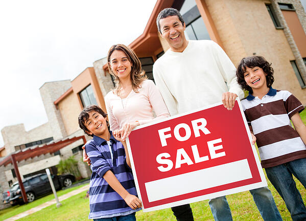 Happy family holding poster of a house for sale