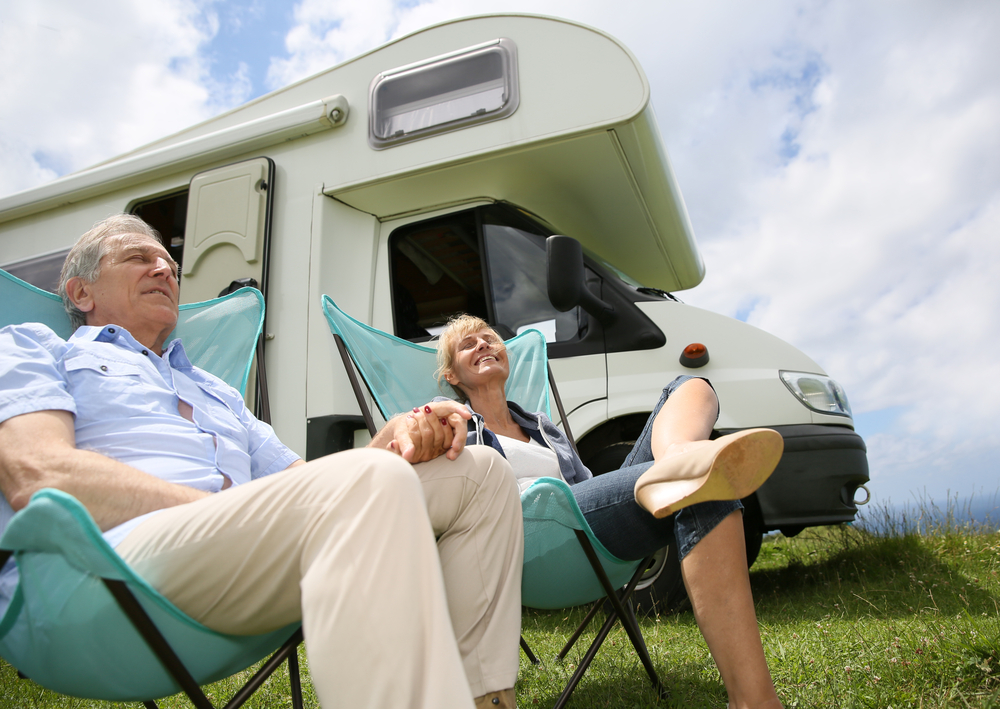 Senior couple relaxing in camping folding chairs, camper in background