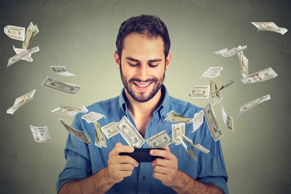 Technology online banking money transfer, e-commerce concept. Happy young man using smartphone with dollar bills flying away from screen isolated on gray wall office background.-1